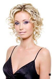 Women's medium length curly hairstyle, with blonde highlight hair color, and without bangs.